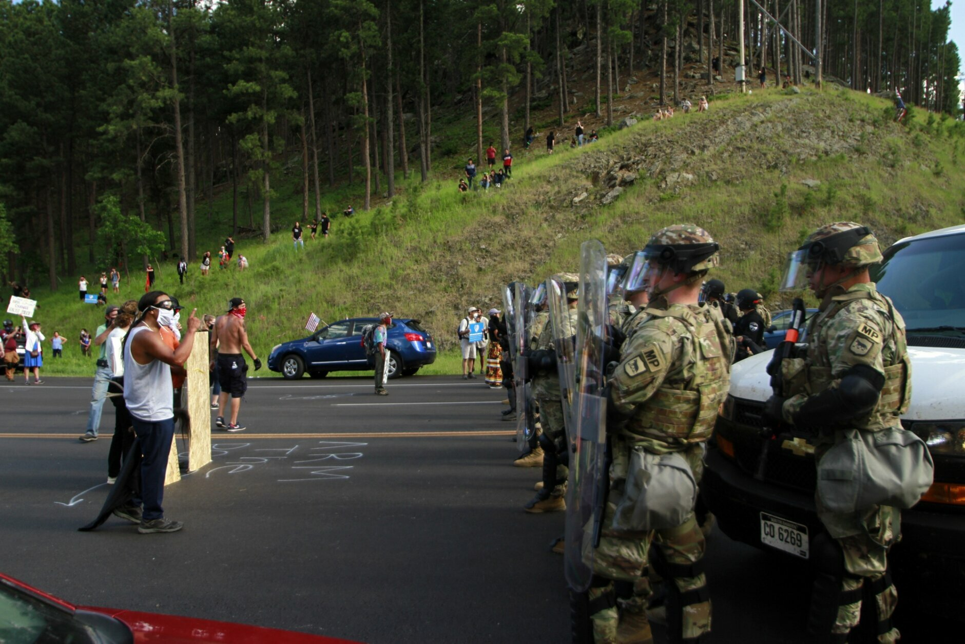 Native American protesters confront a line of law enforcement officers in Keystone, S.D., on the road leading to Mount Rushmore ahead of President Donald Trump's visit to the memorial on Friday, July 3, 2020. (AP Photo/Stephen Groves)