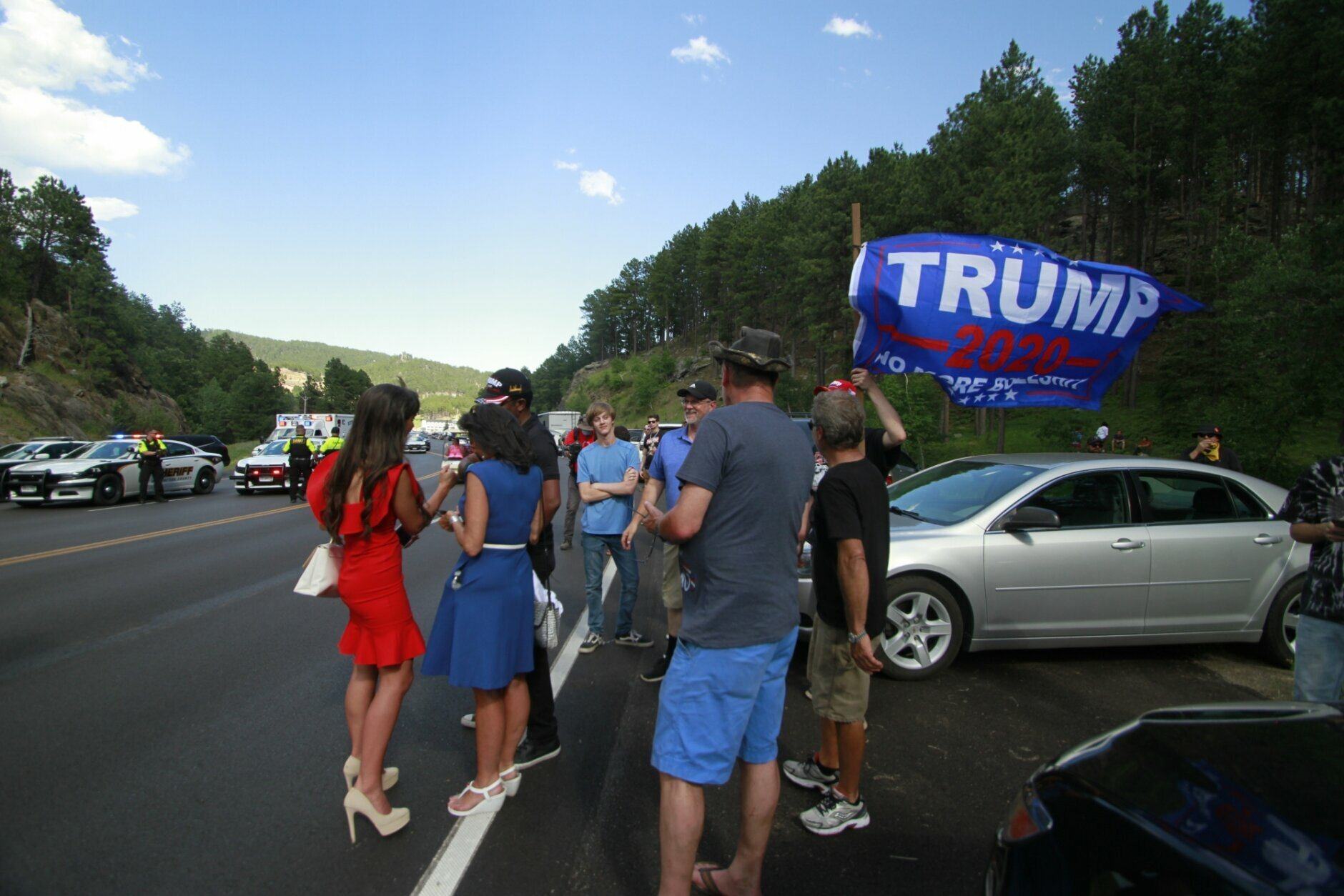 Trump supporters, some who were blocked from reaching Mount Rushmore by a blockade set up by Native American protesters, gather near where protesters clashed with law enforcement officers in Keystone, S.D., Friday, July 3, 2020.. (AP Photo/Stephen Groves)