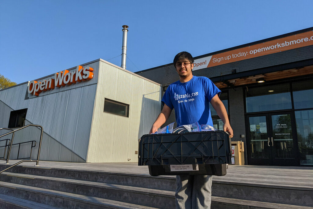 Rockville high schooler Arjun Oberoi carries a bin of 3D-printed PPE from Open Works in Baltimore.