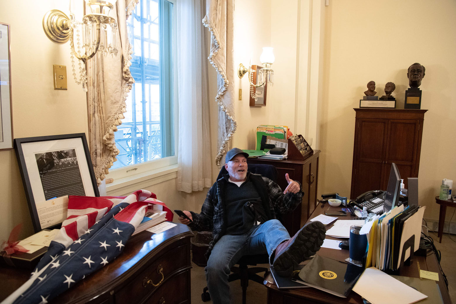 A supporter of US President Donald Trump sits inside the office of US Speaker of the House Nancy Pelosi as he protest inside the US Capitol in Washington, DC, January 6, 2021. - Demonstrators breeched security and entered the Capitol as Congress debated the a 2020 presidential election Electoral Vote Certification. (Photo by SAUL LOEB / AFP) (Photo by SAUL LOEB/AFP via Getty Images)