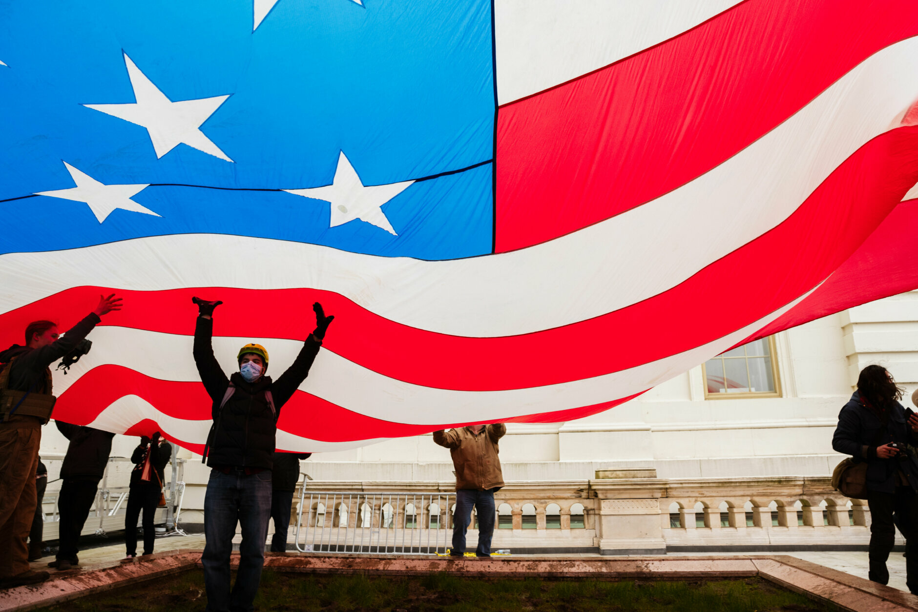WASHINGTON, DC - JANUARY 06: A group of pro-Trump protesters raise a giant America Flag on the West grounds of the Capitol Building on January 6, 2021 in Washington, DC. A pro-Trump mob stormed the Capitol, breaking windows and clashing with police officers. Trump supporters gathered in the nation's capital today to protest the ratification of President-elect Joe Biden's Electoral College victory over President Trump in the 2020 election. (Photo by Jon Cherry/Getty Images)