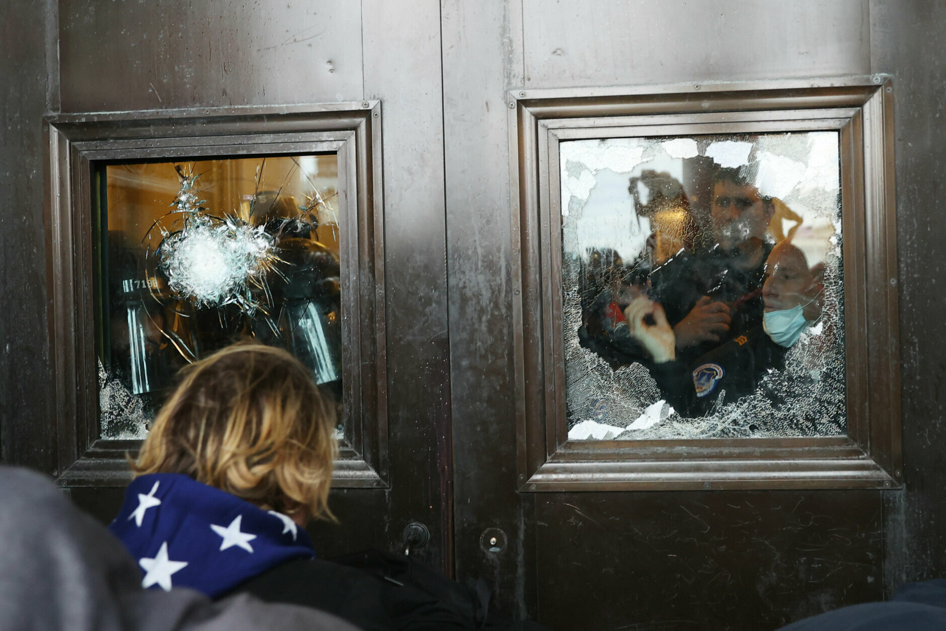 WASHINGTON, DC - JANUARY 06: A Capitol police officer looks out of a broken window as protesters gather on the U.S. Capitol Building on January 06, 2021 in Washington, DC. Pro-Trump protesters entered the U.S. Capitol building after mass demonstrations in the nation's capital during a joint session Congress to ratify President-elect Joe Biden's 306-232 Electoral College win over President Donald Trump. (Photo by Tasos Katopodis/Getty Images)
