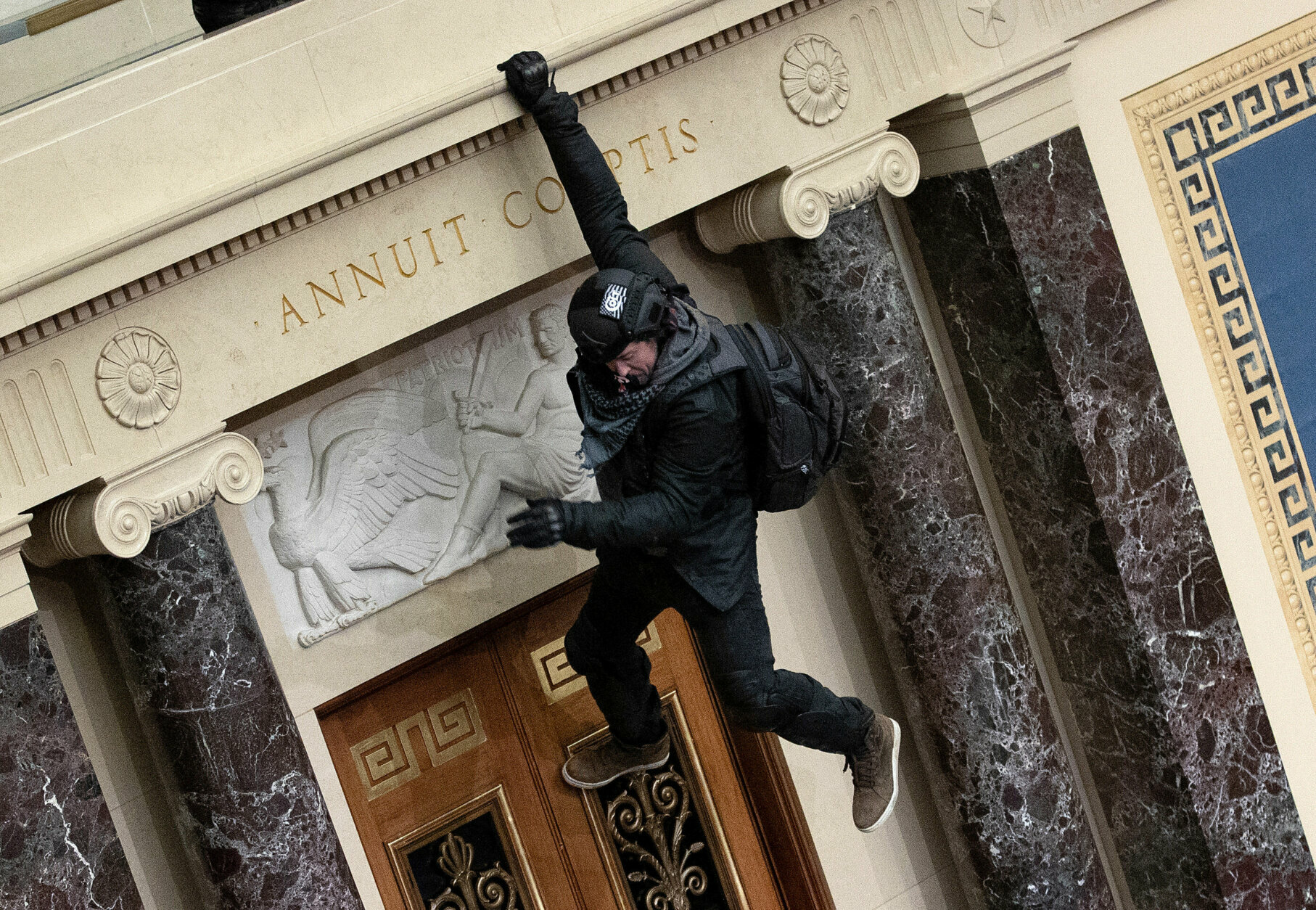 WASHINGTON, DC - JANUARY 06: A protester supporting U.S. President Donald Trump  jumps from the public gallery to the floor of the Senate chamber at the U.S. Capitol Building on January 06, 2021 in Washington, DC. Congress held a joint session today to ratify President-elect Joe Biden's 306-232 Electoral College win over President Donald Trump. A group of Republican senators said they would reject the Electoral College votes of several states unless Congress appointed a commission to audit the election results (Photo by Win McNamee/Getty Images)