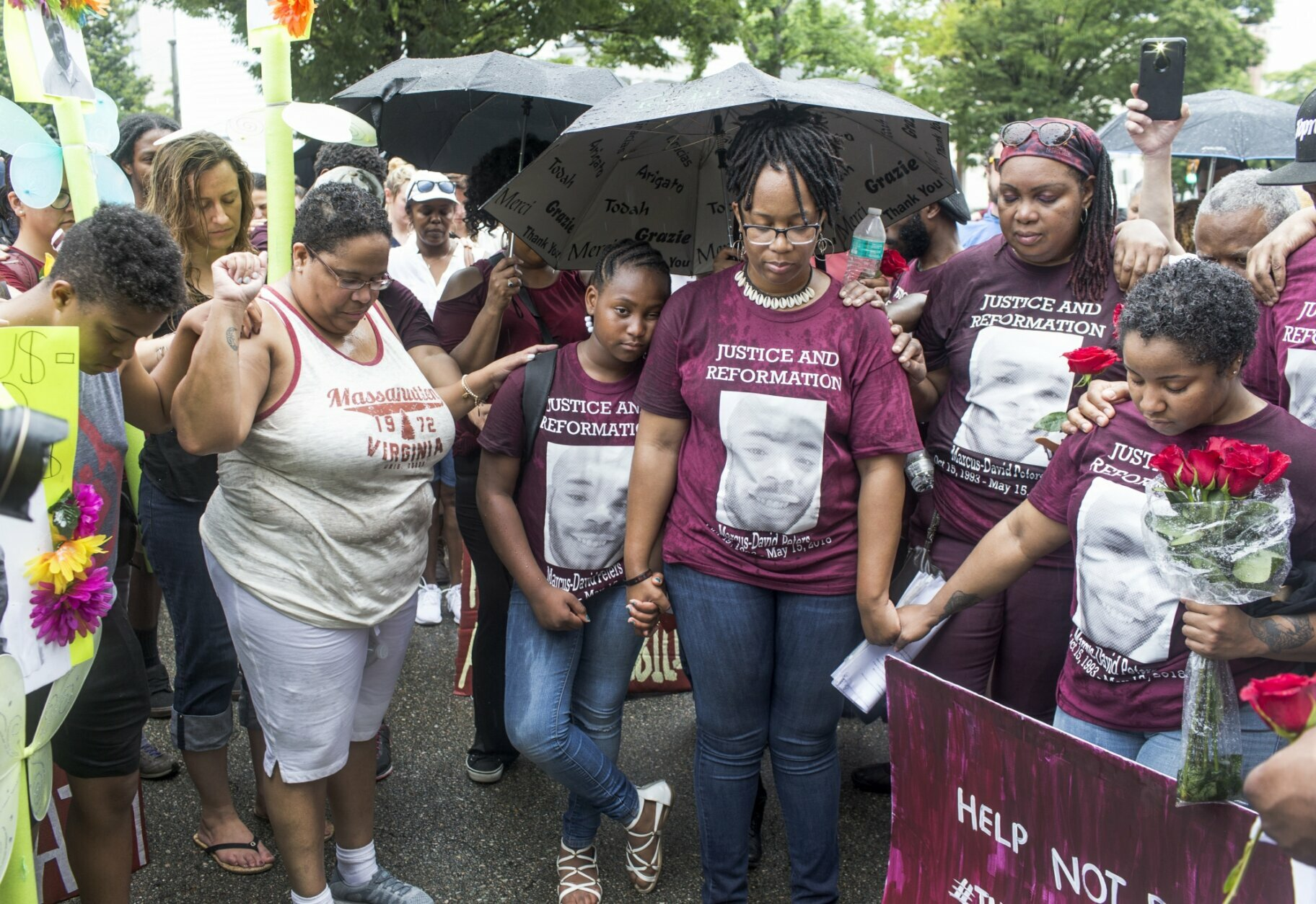 FILE - Family members, including Princess Blanding, center right, sister of Marcus-David Peters, her daughter, Tionna Blanding, 10, center left, cousin Rachel Melvin, right, and others pray after a march for Peters in front of Richmond Police Headquarters in Richmond, Va, on Saturday, June 2, 2018.  An unusually broad field is vying to be the next governor of Virginia as the marquee political contest of 2021 gets into full swing. (Daniel Sangjib Min/Richmond Times-Dispatch via AP)