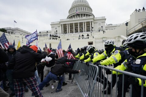 DC police officer gets pinned against door in newly released Capitol riot videos