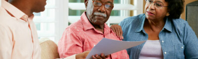 Financial Advisor Talking To Senior Couple At Home Showing Documents