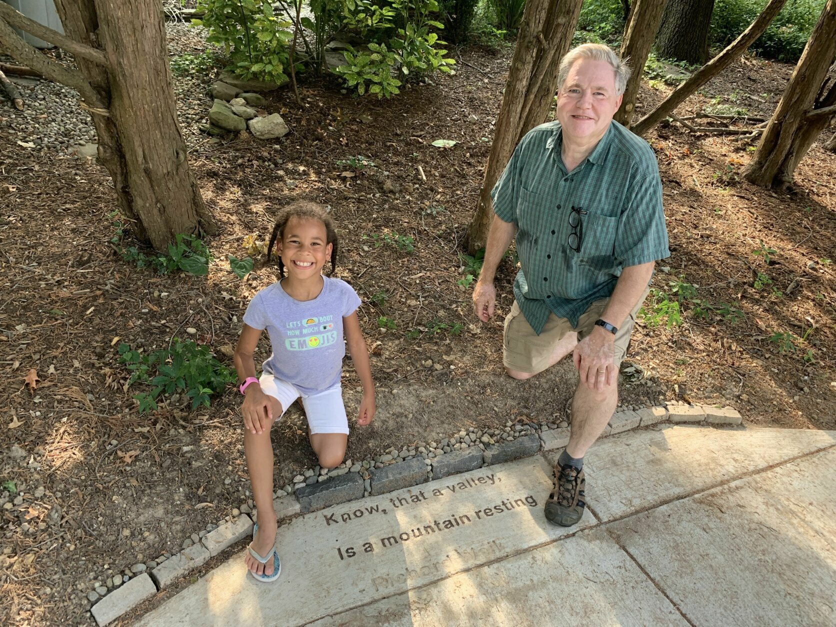 Richard Weil kneels beside the lyrics to a song he wrote, which is now etched on a sidewalk in Takoma Park, Md.