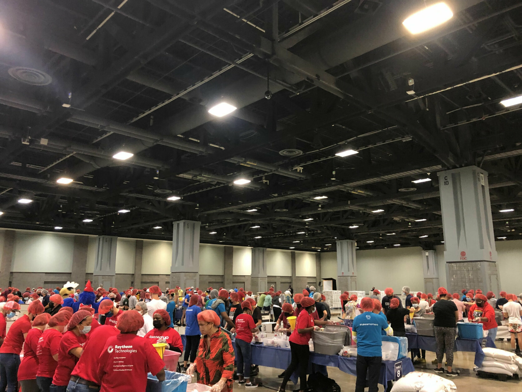 People from fraternities and sororities and community and business groups were among up to 700 volunteers working in shifts to prepare meals for area food banks. (WTOP/Dick Uliano)