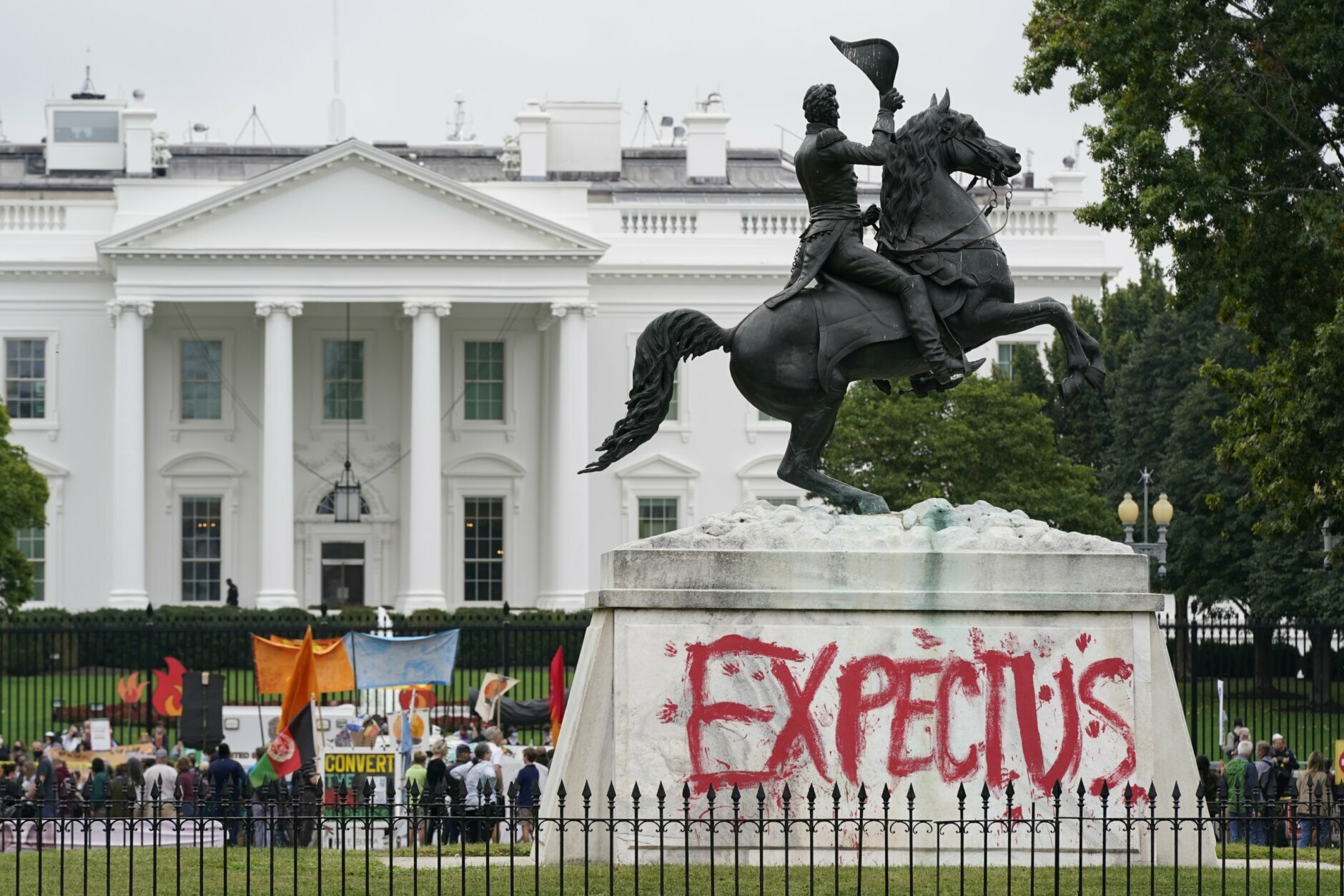 """The words """"Expect us"""" is painted on the bottom of the equestrian statue of President Andrew Jackson in Lafayette Park as protesters gather to urge the Biden administration to do more to combat climate change and ban fossil fuels outside the White House in Washington, Tuesday 12 October 2021.  The words are part of the sentence """"Respect us, or expect us"""" which native women have used while protesting against oil company Enbridge's Line 3 pipeline through Minnesota.  (AP Photo / Patrick Semansky)"""